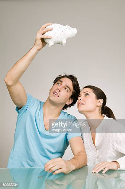Couple looking in piggy bank