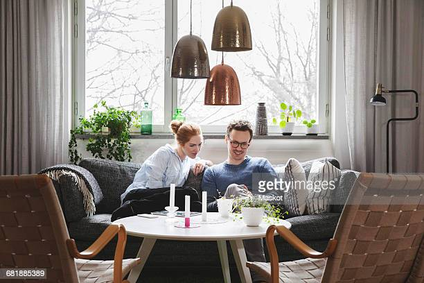 couple looking in smartphone while sitting on sofa at home - scandinavian home stock pictures, royalty-free photos & images