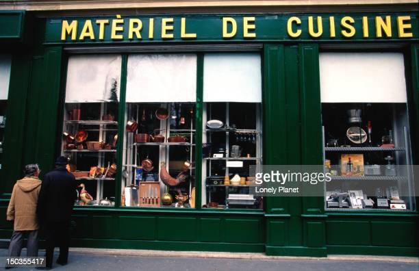 Couple looking in window of Dehillerin cookware shop.