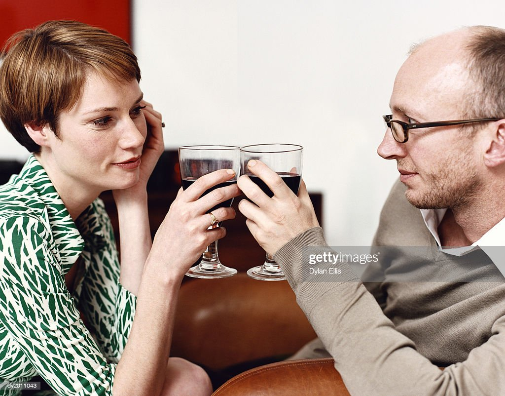 Couple Looking Into Each Other's Eyes and Toasting With Red Wine : Stock Photo