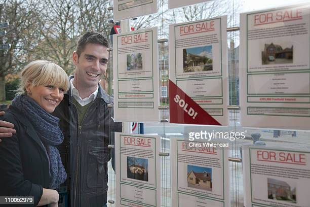 couple looking into estate agents window - real estate sign stock pictures, royalty-free photos & images
