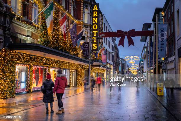 couple looking into shop window at christmas in dublin city centre at henry street - henry street stock pictures, royalty-free photos & images
