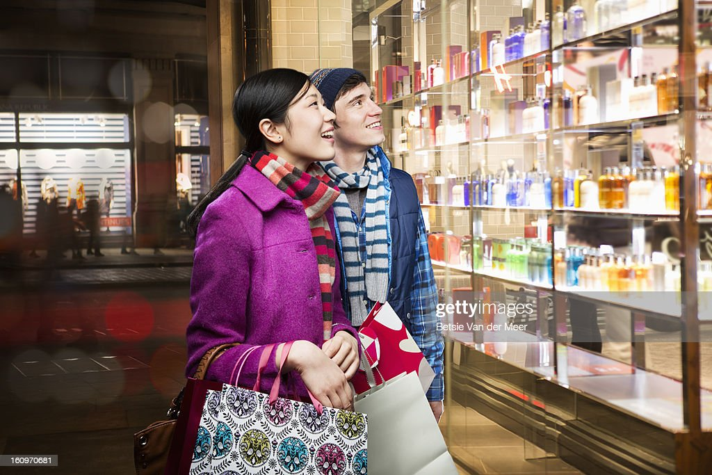 Couple looking into shopwindow in evening. : Foto de stock