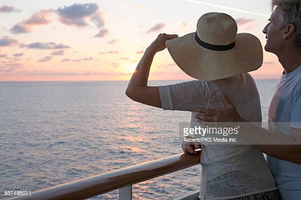 Couple looking out across sea from ship railing
