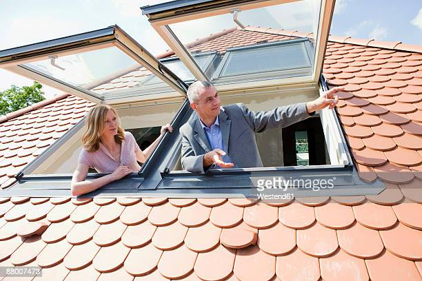 Man and woman looking out dormer windows, man pointing