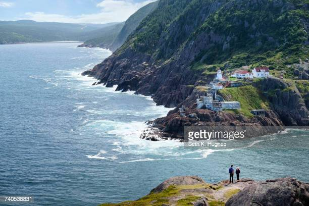 couple looking out from coastal cliff, st johns, newfoundland, canada - st. john's newfoundland stock photos and pictures