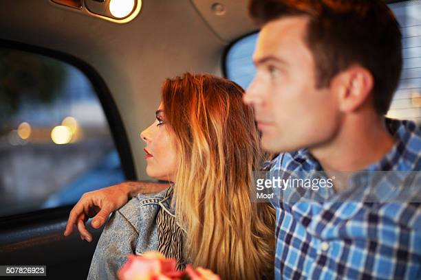 Couple looking out of city taxi window at night