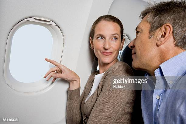 A couple looking out the window of a plane