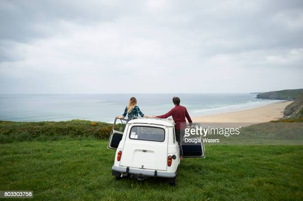 Couple looking out to sea from car on coastal viewpoint.