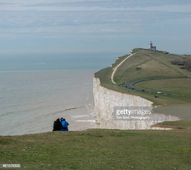 couple looking out to sea - belle tout lighthouse stock photos and pictures
