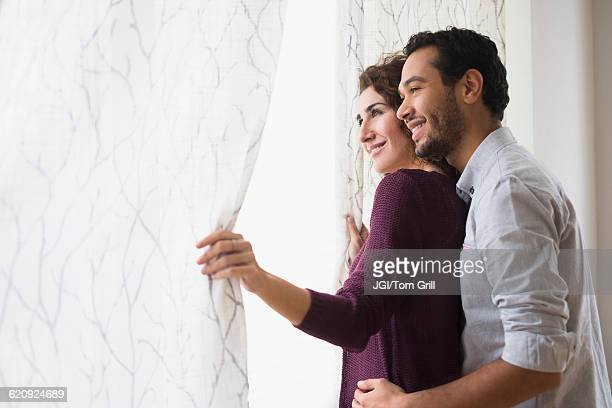 Couple looking out window curtain