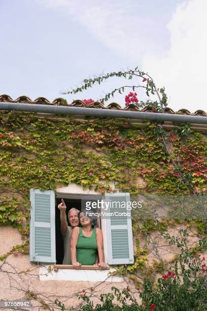 couple looking out window - climat stock pictures, royalty-free photos & images