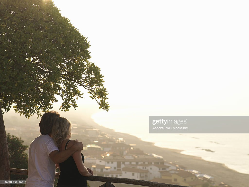 Couple looking over rooftops at Mediterranean, rear view, sunrise : Stock Photo