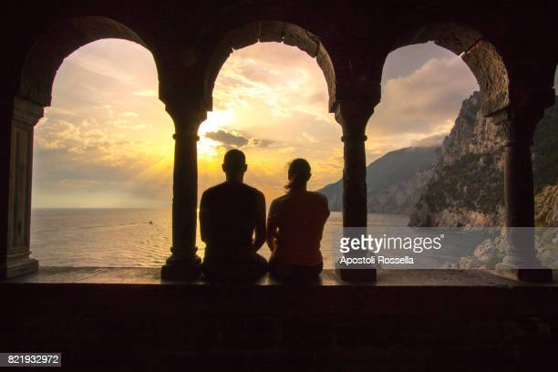 couple looking the sunset at the windows of Portovenere, Liguria