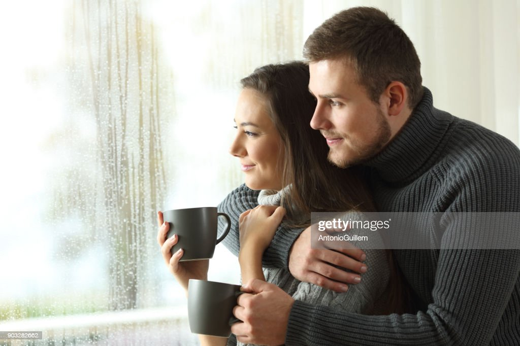 Couple looking through a window in a rainy day : Stock Photo