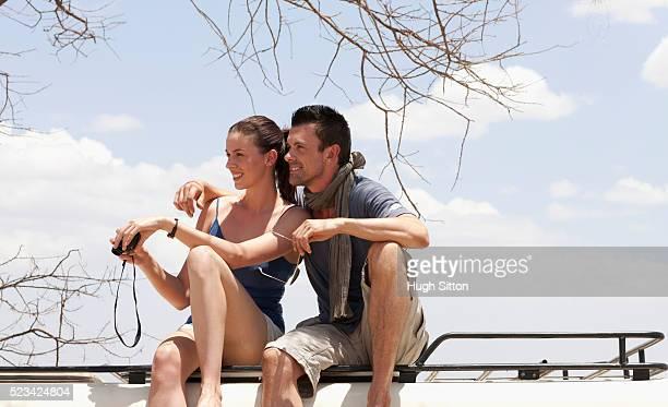 couple looking through binoculars - hugh sitton stock-fotos und bilder