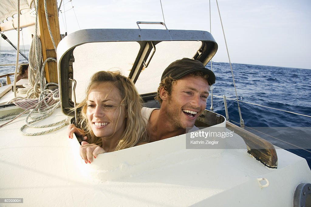 couple looking through hatch on a sailing boat : Stock Photo