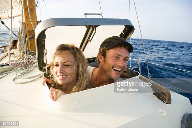 couple looking through hatch on a sailing boat
