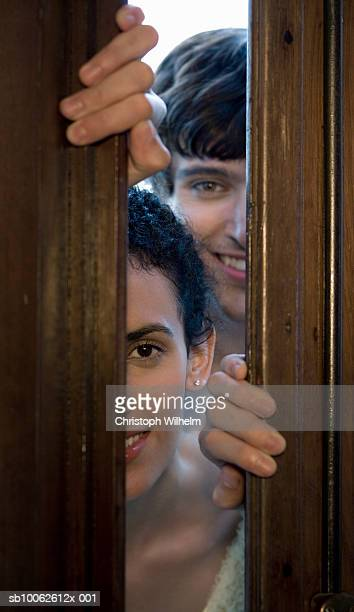 Couple looking through partly open door, portrait