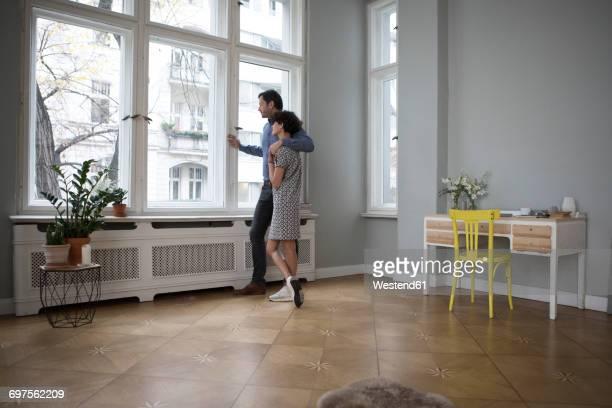 couple looking together through window at home - wohnung stock-fotos und bilder