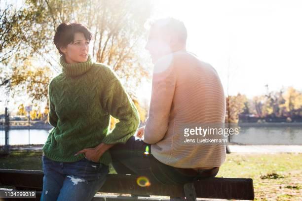 couple looking worried on park bench, strandbad, mannheim, germany - mannheim stock-fotos und bilder