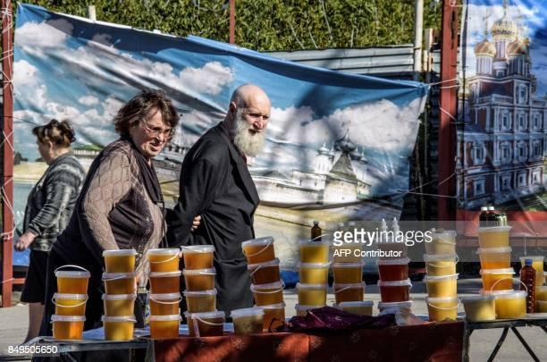 Couple looks at a stand offering honey at a market in Nizhny Novgorod on September 19, 2017. Nizhny Novgorod will host several games of the 2018 FIFA...