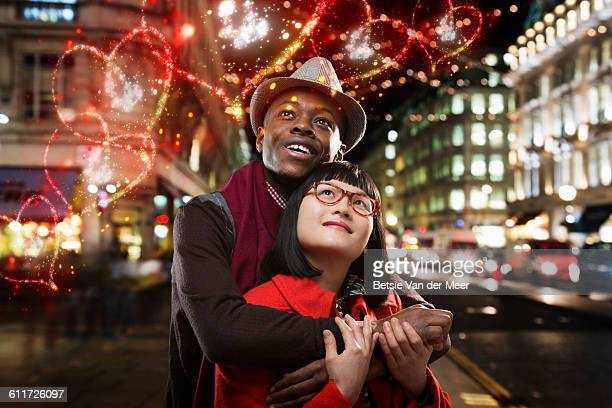 Couple looks at floating hearts passing in street.
