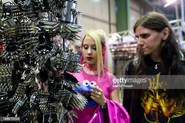 A couple looks at metal thorn collars which are for sale at the Agra festival area on the first day of the annual WaveGotik Treffen or Wave and Goth...