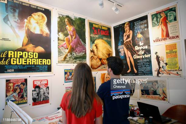 A couple looks at movie posters with French actress Brigitte Bardot during the exhibition The Bardot years 19521973 at Orsay Gallery on June 12 2019...