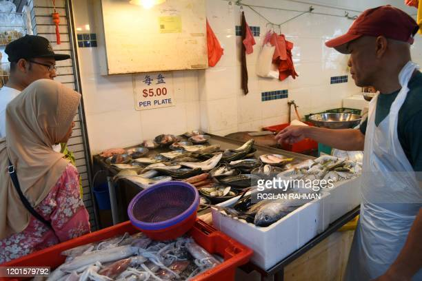 Couple looks at seafood displayed for sale at a wet market in Singapore on February 18, 2020.