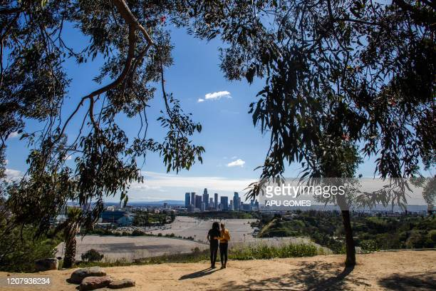 TOPSHOT A couple looks at the Downtown Los Angeles skyline from Elysian Park in Los Angeles on March 21 2020 All 40 million residents of California...