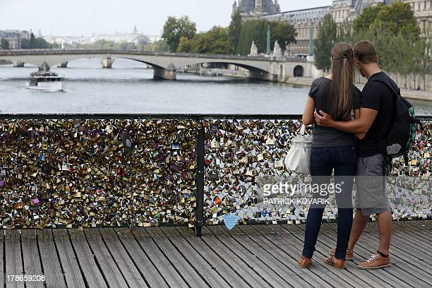 A couple looks at the Pont des Arts where padlocks are attached to the railing on August 30 2013 in Paris Due to security reason authorities consider...