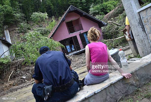 A couple looks at their house damaged by flooding and landslides in Krupanj some 130 kilometres south west of Belgrade on May 20 after the western...