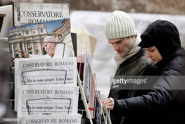 A couple looks at Vatican's newspaper 'L'Osservatore Romano' and calendars outside a kiosk around StPeter's square 26 February 2005 at the Vatican...