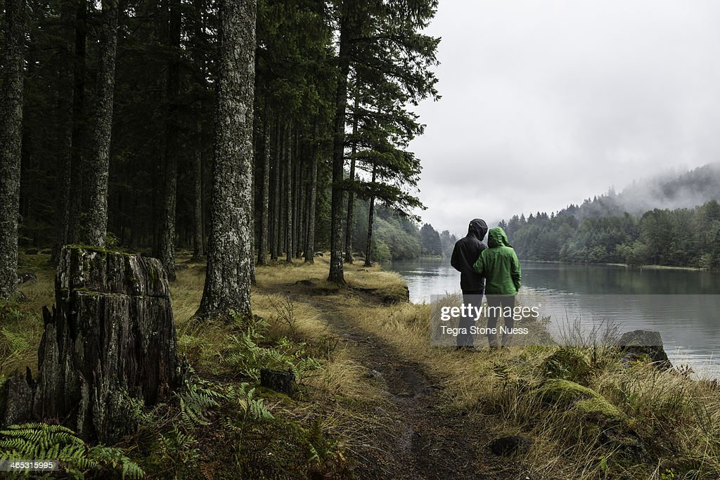 Couple looks out over a misty lake in a forest. : Stock Photo