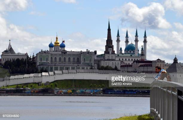 A couple looks over the Kazanka river with the Kazan Kremlin and the KulSharif mosque seen in the background in Kazan on June 9 2018 Kazan is one of...