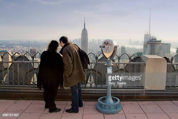 A couple looks south at the New York City skyline from the observation deck at the Top of the Rock at the Rockefeller Center