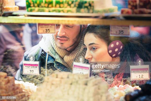 Couple looks trough window at sweets