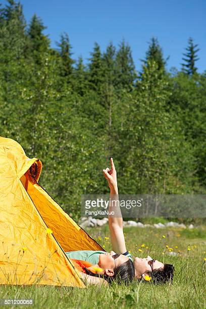 Couple lying by tent, man pointing up