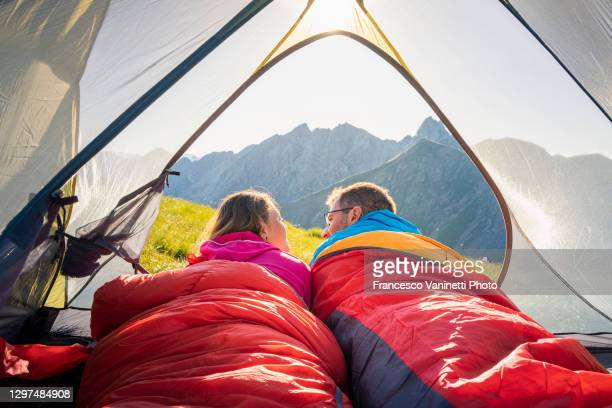 couple lying down in a tent on the mountains, italy. - lying down stock-fotos und bilder