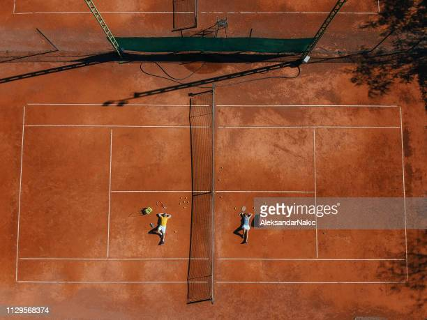 Couple lying down on a tennis court after the match
