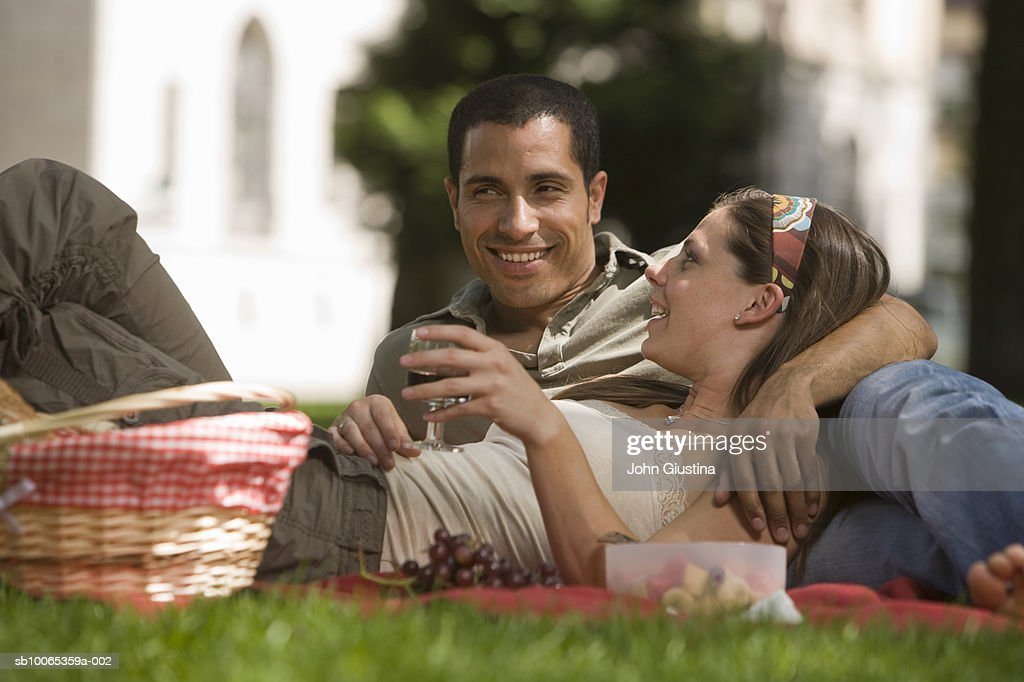Couple lying down picnicking in park : Foto stock