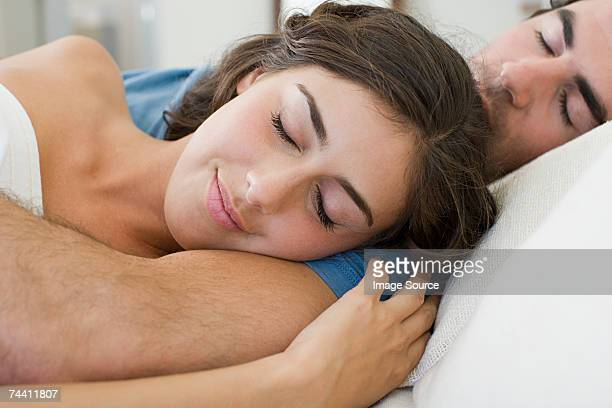 couple lying down - romantic young couple sleeping in bed stock photos and pictures