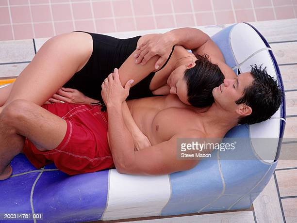 Couple lying, embracing near swimming-pool, elevated view