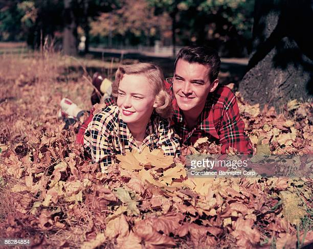 couple lying in autumn leaves - constance bannister stock photos and pictures