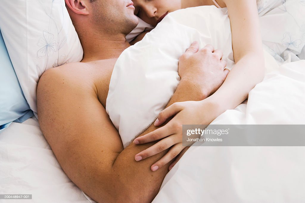 Couple lying in bed, close-up : Stock Photo