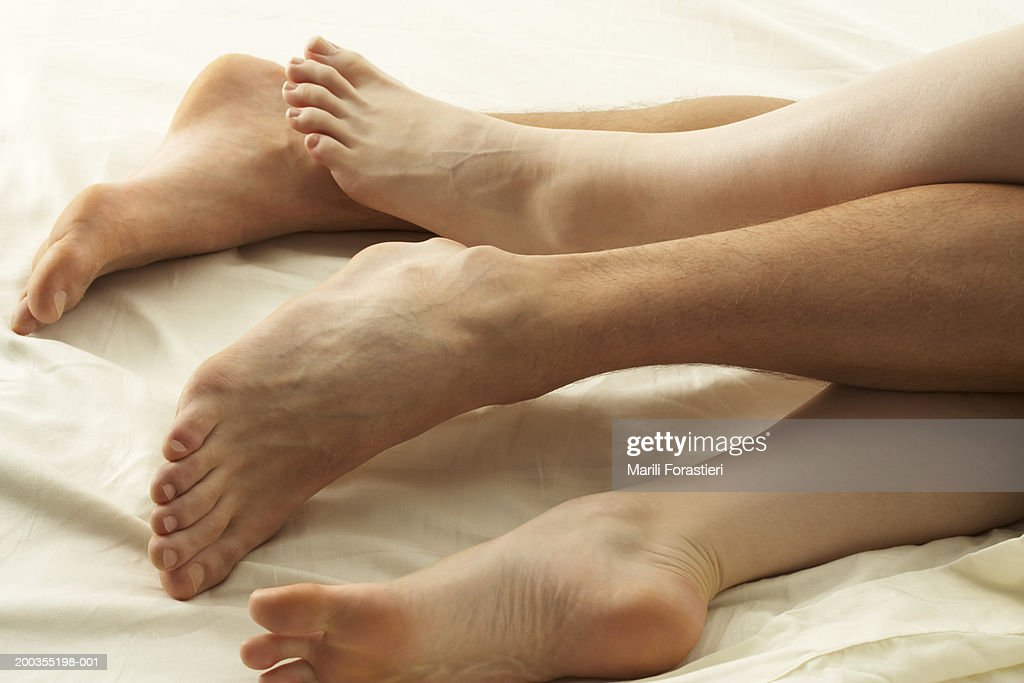 Couple lying in bed, low section, close-up : Stock Photo