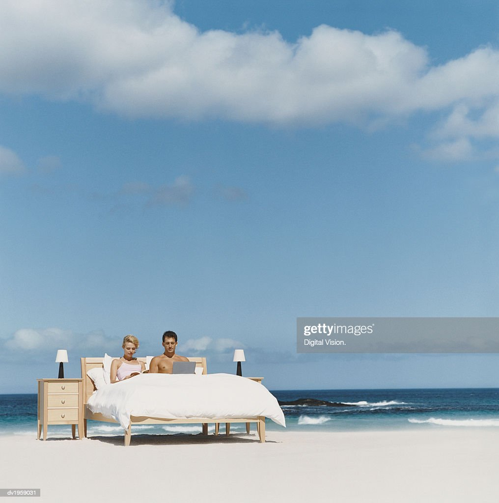 Couple Lying in Bed on a Beach, Man Using His Laptop and Woman Reading a Book : Stock Photo
