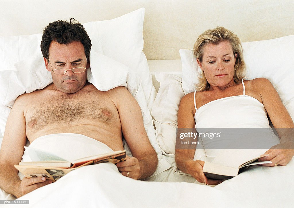 Couple lying in bed, reading : Stockfoto