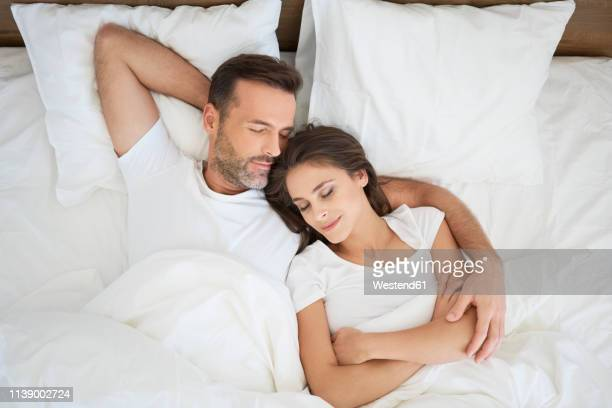 couple lying in bed, sleeping with arms around - couple sleeping stock pictures, royalty-free photos & images